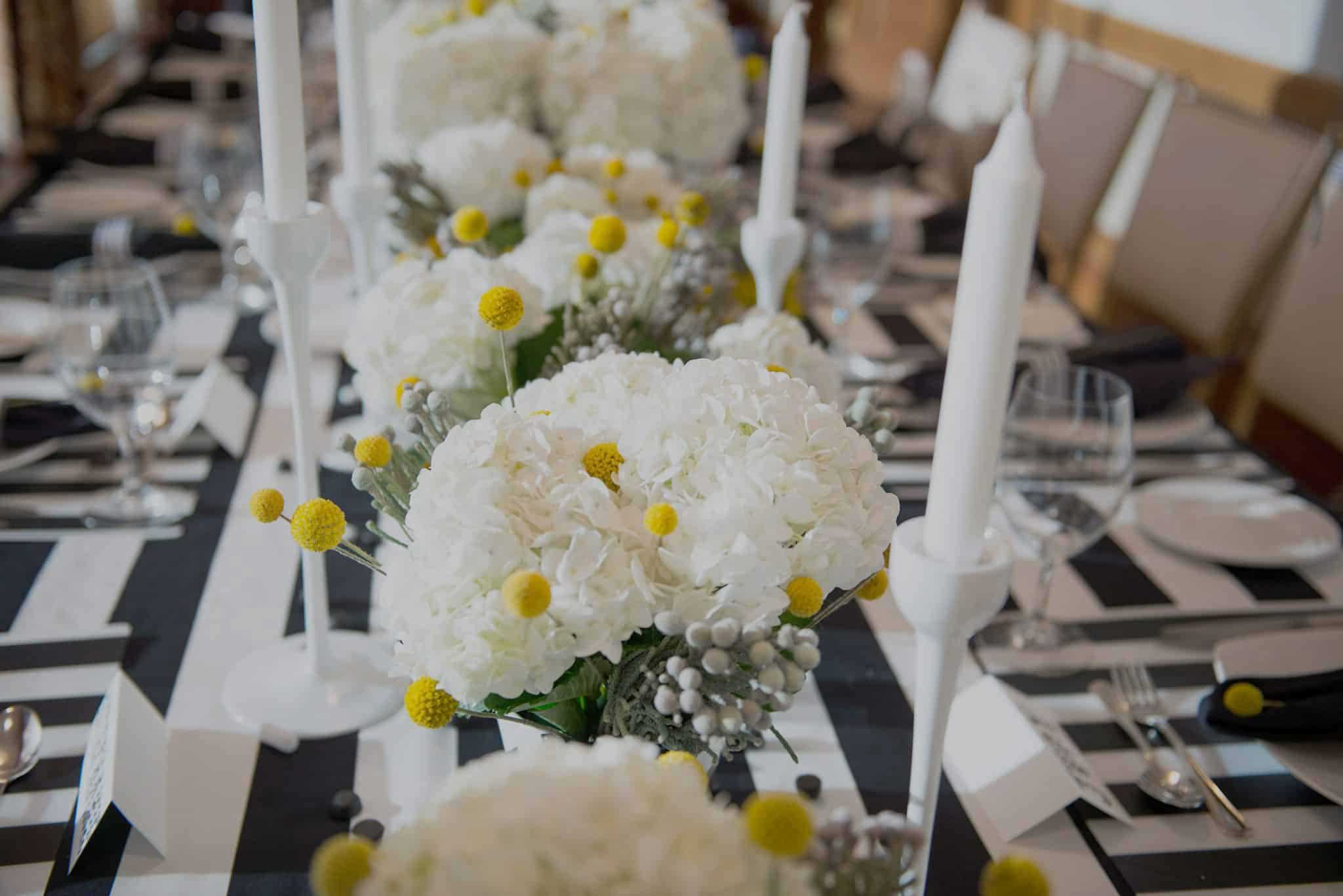 Long rectangular table set with everything in black and white stripes including table cloth, flower pots, place matts, napkin ring. Beautiful repeating centerpieces of white hydrangeas and yellow ball and silver ball shaped accent pieces, white candles in white candle stick holders.